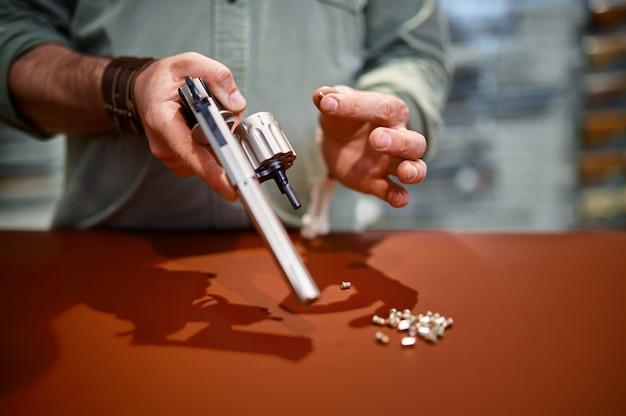 Man herlaad revolver aan de balie in wapenwinkel. wapenwinkelinterieur, munitie- en munitie-assortiment, vuurwapenkeuze, schiethobby en levensstijl, zelfbescherming