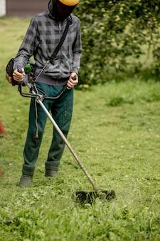 Man het gazon in zijn tuin maaien. tuinman die het gras maait. levensstijl.