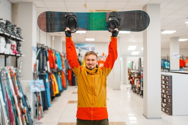 Man hief het bord op voor snowboarden, winkelen in de sportwinkel.