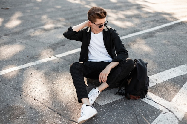 Man hipster in zwarte kleding in witte trendy sneakers met een rugzak in zonnebril zit op straat.