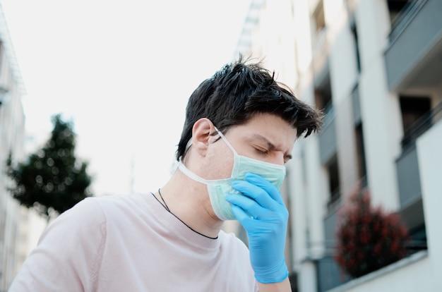 Man hoest in beschermend masker op straat, met luchtvervuiling allergie en longen pijn. jonge man met veiligheidsmasker en handschoenen buitenshuis