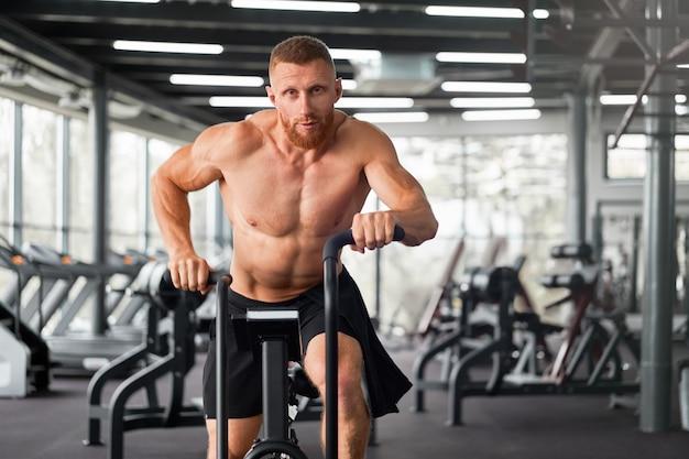 Man hometrainer sportschool fietsen