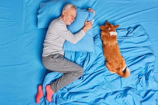 Man, hondeneigenaar van ouderdom slaapt vredig samen met huisdier vormt in bed, draagt pyjama en sokken liggend op een zacht kussen, ziet zoete dromen. rijpe bebaarde man rust op de slaapkamer. mensen sluimeren concept