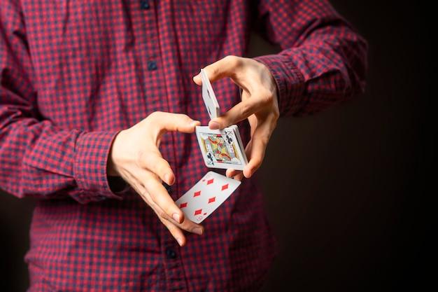 Man houdt aas in mouw en doet trucs met kaarten b