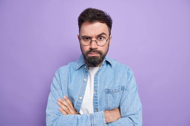 Man houdt armen gevouwen kijkt met zelfverzekerde uitdrukking luistert aandachtig iemands uitleg draagt ronde bril denim overhemd