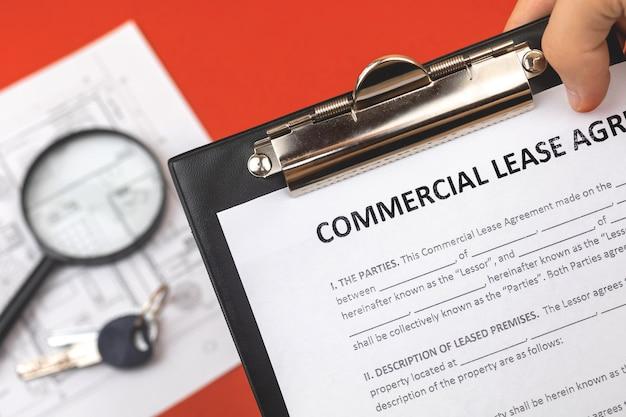 Man houdt commerciële huurovereenkomst in de hand. klembord met officieel document. achtergrond met onroerendgoedpapieren en huissleutels