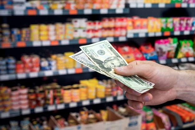 Man houdt dollars in de supermarkt