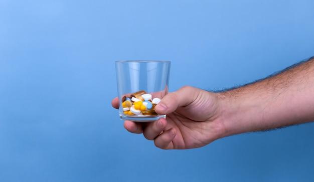 Man houdt dosis pillen in het glas.