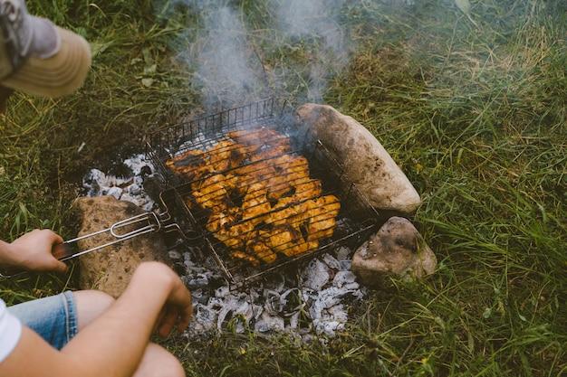 Man houdt een barbecue braden vlees op kolen
