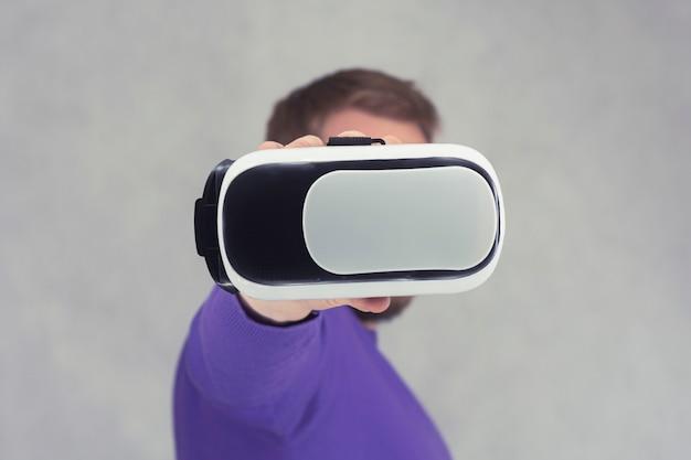 Man houdt een bril in zijn handen voor virtual reality en 360-gradenvideo. vr-helm voor de smartphone op een lichte achtergrond.