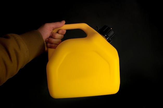 Man houdt een gele plastic bus voor autobrandstof in zijn hand op een zwarte achtergrond. mockup van een container voor vloeistoffen en gevaarlijke brandstoffen.