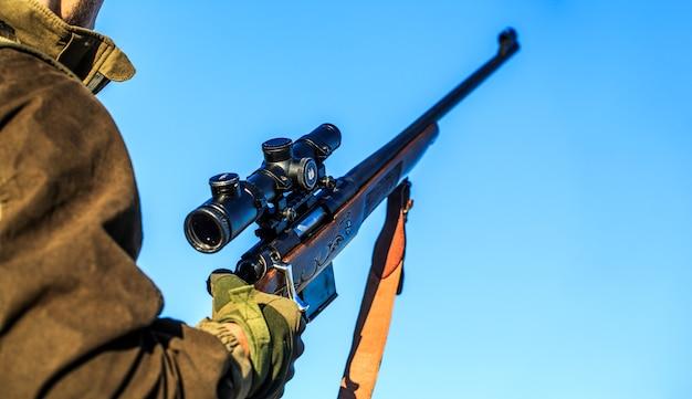 Man houdt een geweer in zijn handen, wapen. shooter waarneming in het doel.