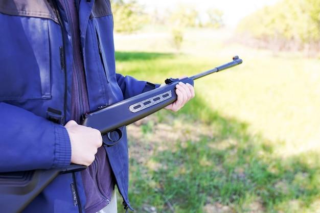 Man houdt een geweer in zijn handen, wapen. waarneming van schutter in het doel. de man is op jacht. detailopname. hunter mikt, jachtgeweer.