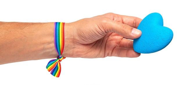 Man houdt een hart in zijn hand. regenbooglint lgbt-trots. homo met blauw hart. geïsoleerd op een wit oppervlak.