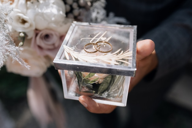 Man houdt een kleine doorzichtige doos met twee trouwringen