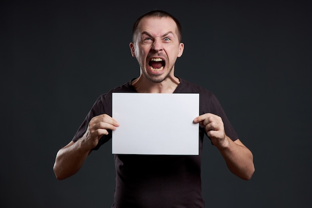 Man houdt een leeg vel posterpapier in zijn handen. glimlach en vreugde, plaats voor tekst, kopieer ruimte