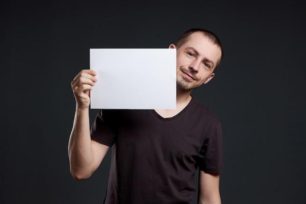 Man houdt een lege poster vel papier in zijn handen. glimlach en vreugde, plaats voor tekst, kopieer ruimte