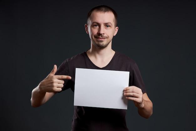 Man houdt een lege poster vel papier in zijn handen.