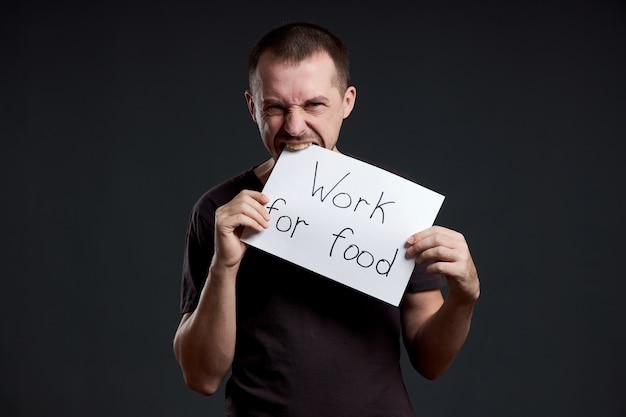 Man houdt een posterpapier vel in zijn handen met de inscriptie ik werk voor voedsel. glimlach en vreugde, plaats voor tekst, kopieer ruimte