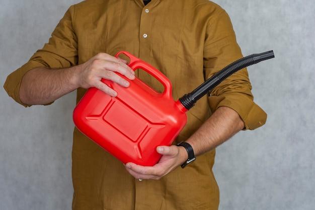Man houdt een rode plastic gasfles in zijn handen.