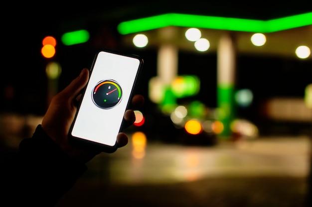 Man houdt een smartphone met een digitale brandstofmeter op het scherm tegen de achtergrond van een nachttankstation voor een auto.