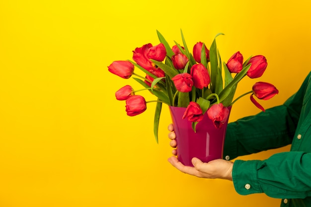 Man houdt een vaas in zijn handen met een boeket van rode tulpen. levering van bloemen en cadeaus voor moederdag