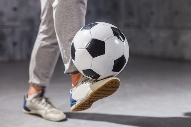 Man houdt een voetbal op zijn been. detailopname
