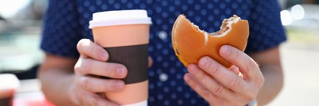 Man houdt glas met warme koffie en hamburger in zijn hand fast food concept