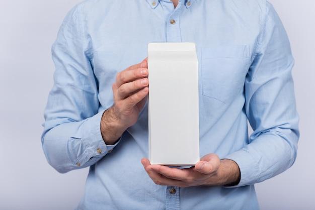 Man houdt grote pak melk of sap. kopieer ruimte, bespot
