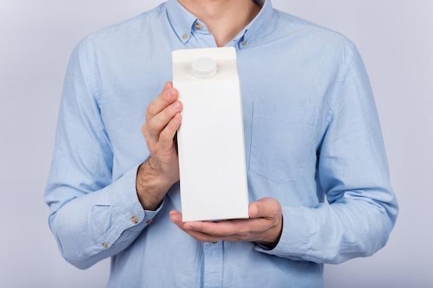 Man houdt grote pak melk of sap.