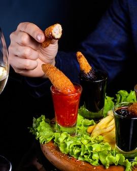Man houdt halfgebeten gebakken garnalen geserveerd met saus en frietjes
