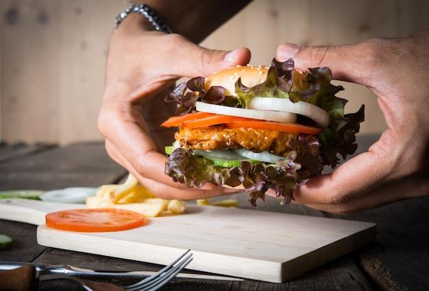 Man houdt hamburger met handen en aardappelchips.