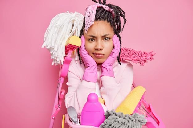 Man houdt handen op gezicht heeft een ongelukkige uitdrukking en moet huishoudelijk werk doen omringd door schoonmaakmiddelen poseert alleen binnenshuis