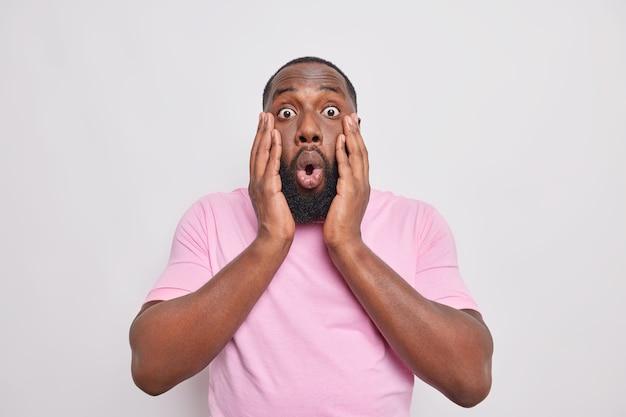 Man houdt handen op gezicht reageert op iets angstaanjagends overvallen met nieuws draagt casual t-shirt