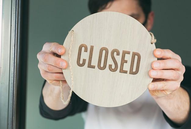 Man houdt het houten bord vast met de tekst: closed