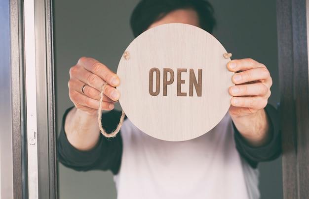 Man houdt het houten bord vast met de tekst: open