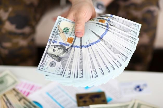 Man houdt in de hand grote dikke pak amerikaans geld
