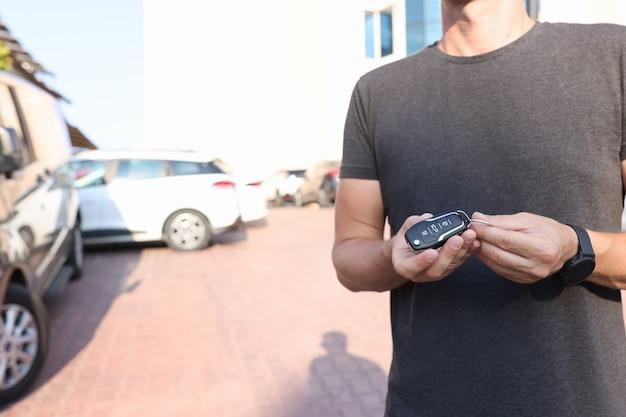Man houdt in handen drukknop afstandsbediening van auto afstandsbediening auto concept