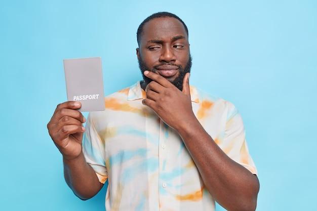 Man houdt kin vast kijkt aandachtig naar paspoort denkt aan reizen naar het buitenland gekleed in verwassen overhemd