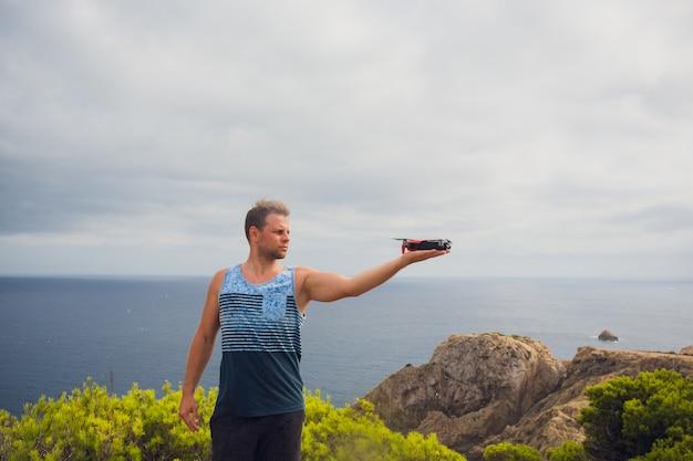 Man houdt kleine compacte drone in zijn handen. piloot lanceert quadrupter vanuit zijn handpalm. drone klaar om op gps te gaan.
