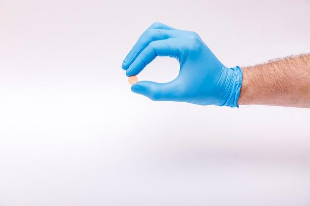 Man houdt medische pil in de hand. coronavirusprobleem en covid-19-beschermingsconcept.