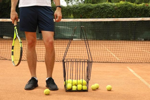Man houdt racket op gravel met mandje met tennisballen