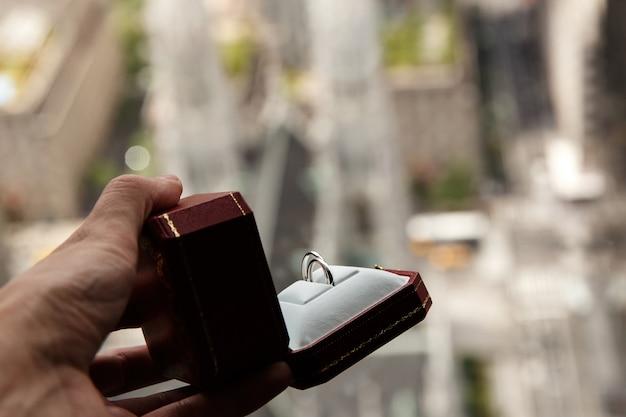 Man houdt rode doos met trouwringen