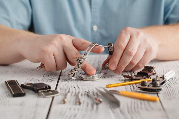 Man houdt roestvrij horloge en verandert horlogeband met de hand