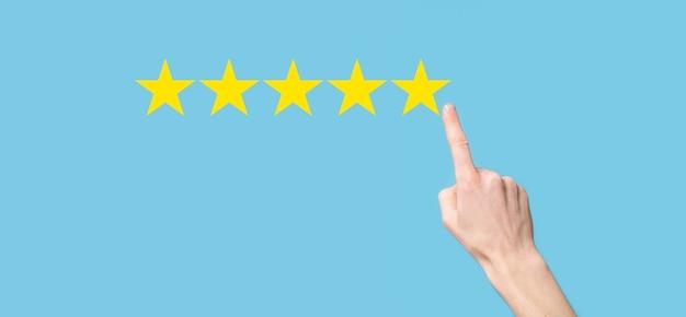 Man houdt slimme telefoon in handen en geeft positieve beoordeling, pictogram vijf sterren symbool om de beoordeling van het bedrijfsconcept op blauwe achtergrond te verhogen. klantenservice-ervaring en zakelijke tevredenheidsenquête.