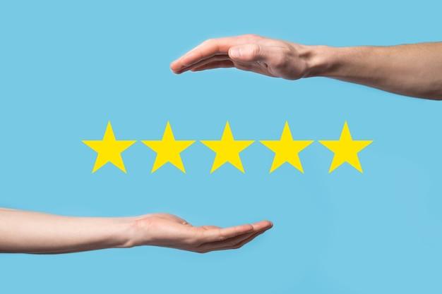Man houdt slimme telefoon in handen en geeft positieve beoordeling, pictogram vijf sterrensymbool om de beoordeling van bedrijfsconcept op blauwe achtergrond te verhogen. klantenservice ervaring en zakelijke tevredenheidsenquête.