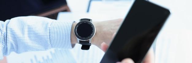 Man houdt smartphone in zijn hand en kijkt naar smart watch smart watch voor gezondheidsmonitoring