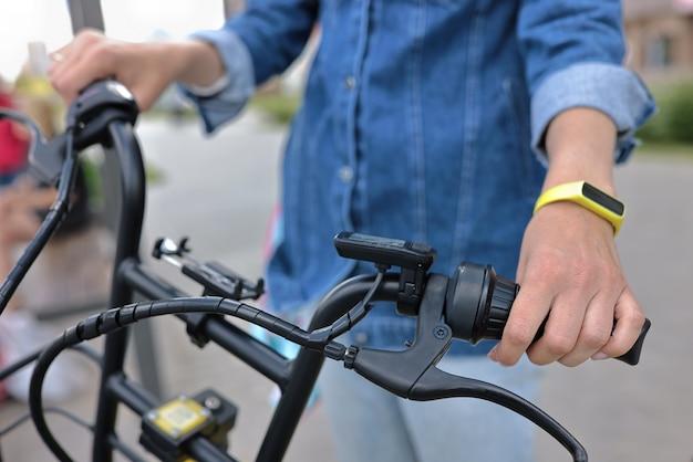 Man houdt stuur van zwarte fiets in straat.