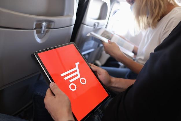 Man houdt tablet vast en doet online aankopen terwijl hij in de cabine van het vliegtuig zit