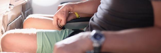 Man houdt vrouw hand in passagiersstoelen in vliegtuigcabine